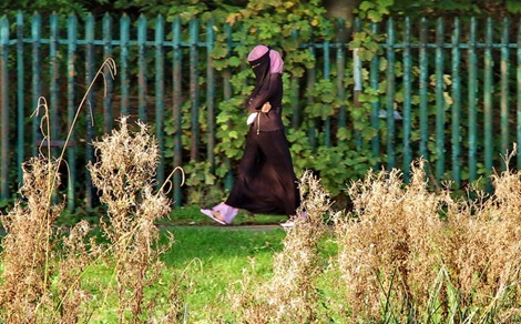 Niqab-wearing lady strolls on the riverside near Belgrave Lock in Leicester